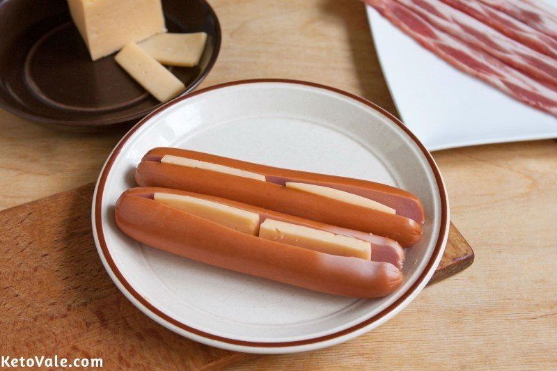 Insert cheese inside hot dogs