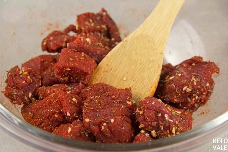 mélanger les bouchées de bœuf avec des épices